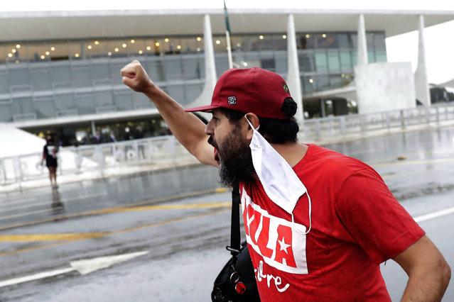 """A demonstrator shouts """"Free Lula"""" during a protest commemorating the Supreme Court's decision to suspend proceedings against former Brazil's President Luiz Inacio Lula da Silva, in front of the Planalto Presidential Palace in Brasilia, Brazil, Monday, March 8, 2021. (Photo by Eraldo Peres/AP Photo)"""