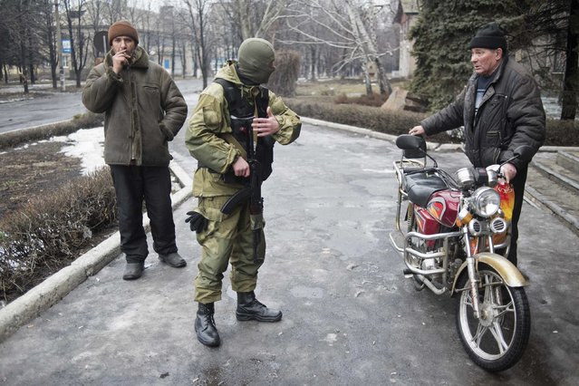 A member of the Ukrainian armed forces offers local residents to join people who are boarding a bus and fleeing from military conflict in Debaltseve, February 3, 2015. (Photo by Sergey Polezhaka/Reuters)