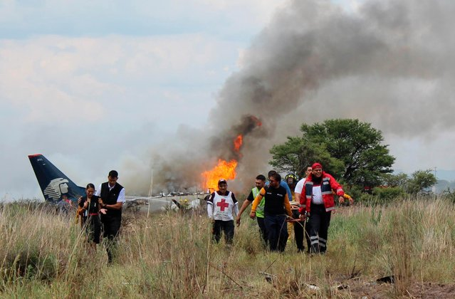 In this photo released by Red Cross Durango communications office, Red Cross workers and rescue workers carry an injured person on a stretcher, right, as airline workers, left, walk away from the site where an Aeromexico airliner crashed in a field near the airport in Durango, Mexico, Tuesday, July 31, 2018. The jetliner crashed while taking off during a severe storm, smacking down in a field nearly intact then catching fire, and officials said it appeared everyone on board escaped the flames. (Photo by Red Cross Durango via AP Photo)
