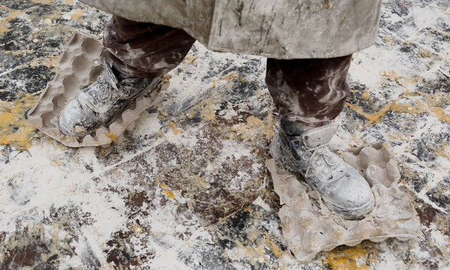 "A reveller wears eggs boxes on the soles of his shoes to enhance grip in the battle of ""Enfarinats"", a flour fight in celebration of the Els Enfarinats festival on December 28, 2015 in Ibi, Spain. (Photo by Pablo Blazquez Dominguez/Getty Images)"