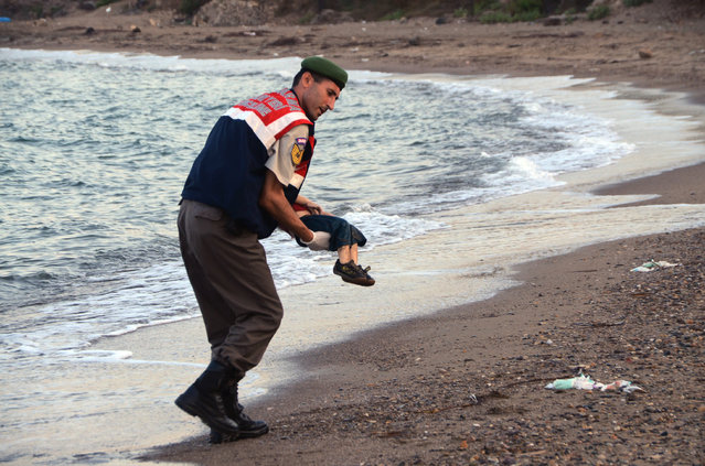 A paramilitary police officer carries the lifeless body of Aylan Kurdi, 3, after a number of migrants died and a smaller number were reported missing after boats carrying them to the Greek island of Kos capsized, near the Turkish resort of Bodrum early Wednesday, September 2, 2015. The family — Abdullah, his wife Rehan and their two boys, 3-year-old Aylan and 5-year-old Galip – embarked on the perilous boat journey only after their bid to move to Canada was rejected. The tides also washed up the bodies of Rehan and Galip on Turkey's Bodrum peninsula Wednesday, Abdullah survived the tragedy. (Photo by AP Photo/DHA)