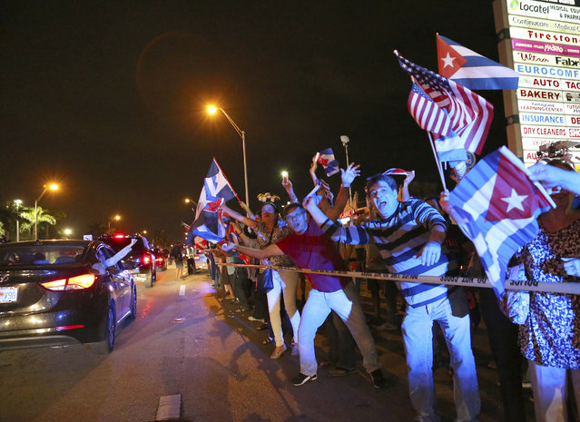 The Cuban community in Miami celebrates the announcement that Fidel Castro died in front of La Carreta Restaurant, early Saturday, November 26, 2016, in Miami. Within half an hour of the Cuban government's official announcement that former President Fidel Castro had died, Friday, Nov. 25, 2016, at age 90, Miami's Little Havana teemed with life – and cheers. (Photo by David Santiago/El Nuevo Herald via AP Photo)