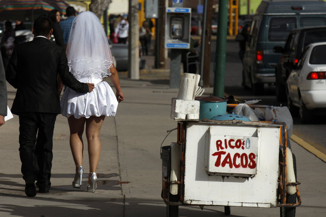 """A newly married couple walks past a taco stand with the sign reading """"Yummy Tacos"""" after a mass wedding in Ciudad Juarez February 14, 2012. The mass wedding ceremony was held for 3,121 couples on Valentine's day. (Photo by Jose Luis Gonzalez/Reuters)"""