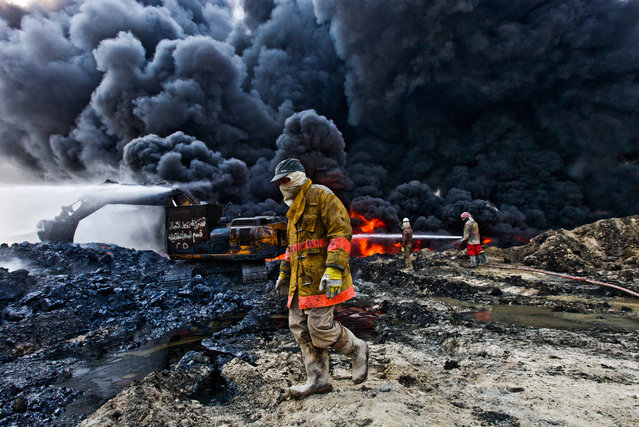 Firefighting teams try to extinguish an oil fire November 27, 2016 as smoke billows from one of the remaining oil wells set ablaze by ISIL in their retreat from Qayyarah at the start of the Mosul offensive which began more than a month prior. (Photo by Byron Smith/ZUMA Wire/Rex Features/Shutterstock)