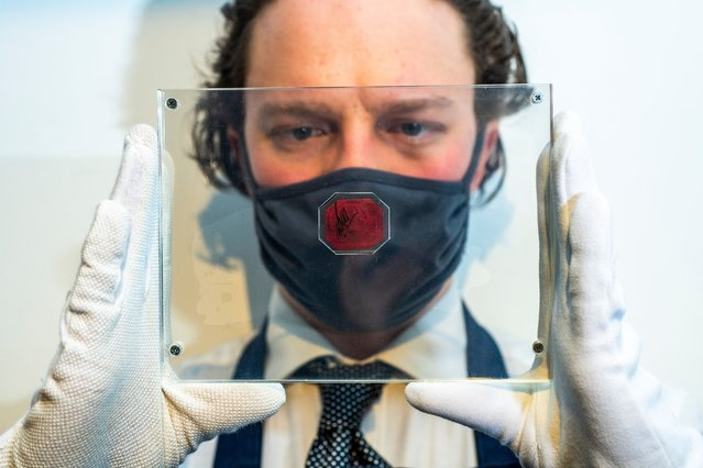 An auction worker poses with a British Guiana One-Cent Magenta stamp as it is displayed at Sotheby's Auction House in London, Britain, 28 April 2021. The stamp is the only known survivor of its kind and was created as a contingency in 1856 when a shortage of stamps usually imported from England threatened to disrupt the postal service throughout British Guiana. With an estimate of 10 to 15 Million UIS Dollars, it will be auctioned at Sotheby's New York on 08 June 2021. (Photo by Jill Mead/The Guardian)