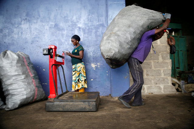 A man lifts a bag containing wastes from a weighing machine at the Wecycler recycling centre in Ebute Metta district in Lagos, Nigeria, July 28, 2016. (Photo by Akintunde Akinleye/Reuters)