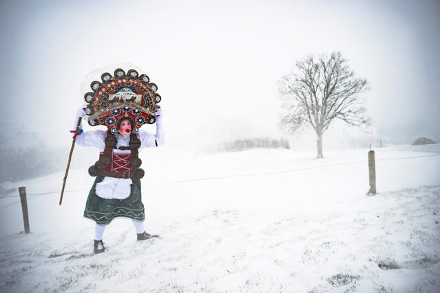 A so-called Silvesterchlaus (New Year Clause) holds on to his hat during heavy winds on his way in Waldstatt, Switzerland, 13 January 2016, to offer their best wishes for the New Year (following the Julian calendar) to the farmers in this region. After their performance of singing and dancing the Silvesterchlaeuse receive hot drinks. (Photo by Gian Ehrenzeller/EPA)