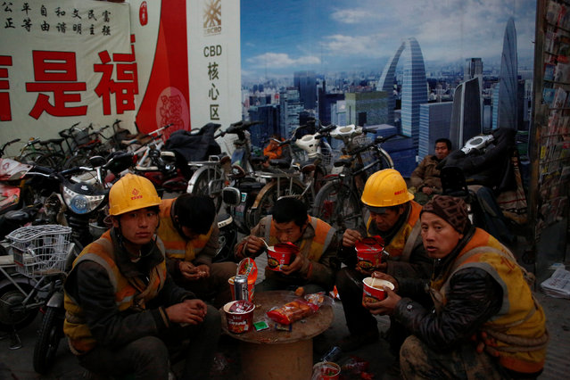 Workers eat street food at a stall outside a construction site at the end of their shift in Beijing, China December 6, 2016. (Photo by Thomas Peter/Reuters)