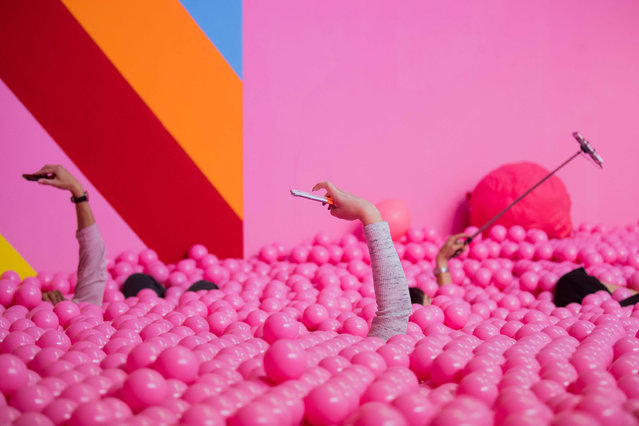 """Visitors to the Supercandy Pop- Up Museum make selfies in a ball bath in Cologne, Germany on September 27, 2018. Until 30.12.2018 the 20 walk- in installations can be seen and experienced in the """"Made- for- Instagram"""" exhibition in Cologne- Ehrenfeld. (Photo by Rolf Vennenbernd/DPA)"""