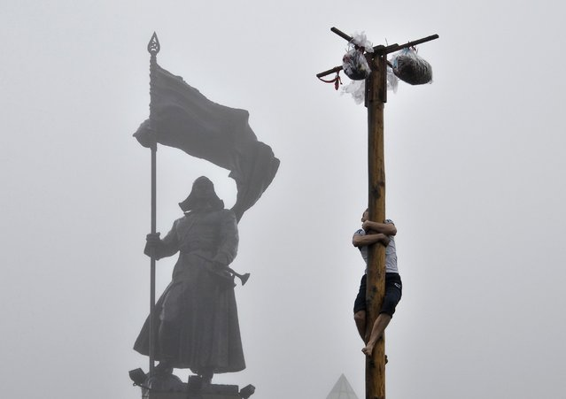 A man tries to climb a wooden pole to get a prize during Maslenitsa celebrations in front of a monument of a revolutionary soldier in Russia's far eastern city of Vladivostok February 22, 2015. Maslenitsa is a pagan holiday marking the end of winter celebrated with pancake eating and shows of strength. (Photo by Yuri Maltsev/Reuters)