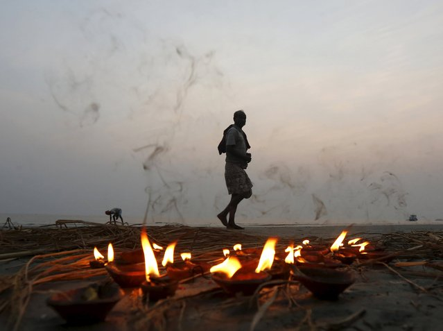 "A Hindu pilgrim walks past a row of lighted lamps after taking a holy dip at the confluence of the river Ganges and the Bay of Bengal at Sagar Island, south of Kolkata, India, January 12, 2016. Hindu monks and pilgrims are making their annual trip to Sagar Island for the one-day festival of ""Makar Sankranti"" on January 15. (Photo by Rupak De Chowdhuri/Reuters)"
