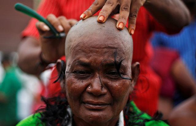 A supporter of Tamil Nadu Chief Minister Jayalalithaa Jayaraman gets her head shaved near Jayalalithaa's burial site in Chennai, India, December 7, 2016. (Photo by Adnan Abidi/Reuters)
