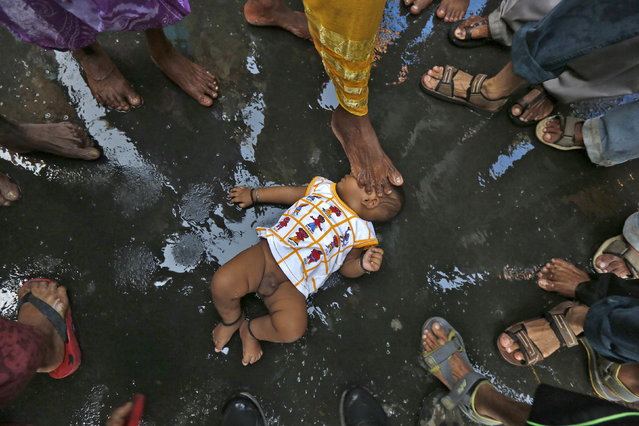 A Hindu holy man (not pictured) touches an infant with his foot as part of a ritual to bless him during a religious procession to mark the Gajan festival in Kolkata, April 12, 2016. (Photo by Rupak De Chowdhuri/Reuters)