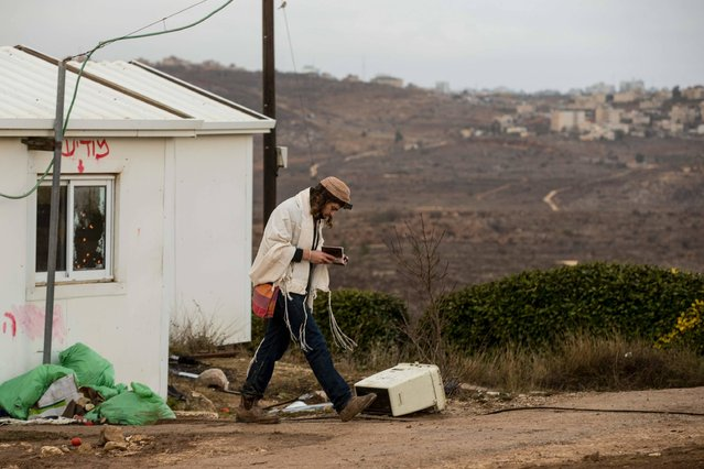 A young Israeli settler walks while praying in the settlement outpost of Amona, which was established in 1997 and built on private Palestinian land, in the Israeli-occupied West Bank on December 15, 2016. Residents of athewildcat Jewish settlement rejected a proposal to leave voluntarily, raising fears of violence as an evacuation deadline nears. The Amona outpost, home to some 40 families, is under a High Court order to be evacuated by December 25 since it was found to have been built on private Palestinian land. (Photo by Jack Guez/AFP Photo)