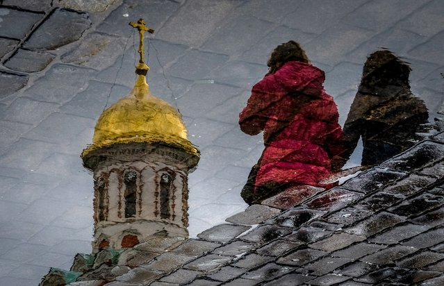 Women are reflected in a puddle as they walk across Red Square in Moscow, Russia on April 26, 2018. (Photo by Yuri Kadobnov/AFP Photo)