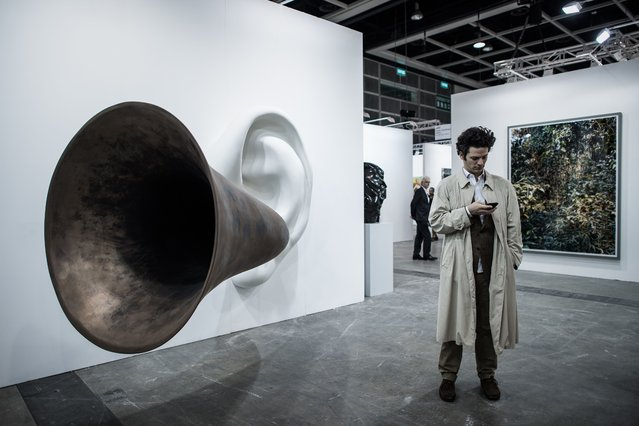 A man checks his mobile phone next to an artwork by US conceptual artist John Anthony Baldessari (L) during the opening of the Art Basel art fair for a VIP preview in Hong Kong on March 13, 2015. (Photo by Philippe Lopez/AFP Photo)