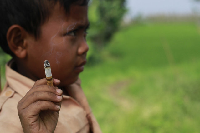 Seven-year-old Dihan Awallidan from Garut, West Java, is not like other boys his age. While most children crave chocolate and candy, Dihan is addicted to cigarettes. The second-grader picked up the habit at the age of 3 and now smokes up to three packs a day, using the pocket money he gets from his enabling parents to feed his addiction. (Photo by Rezza Estily/JG Photo)