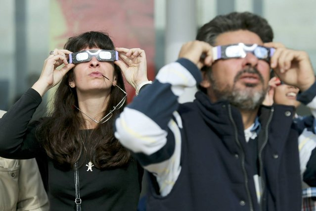 People use special spectacles allowing them to watch a rare solar eclipse showing the Sun partially blocked by the Moon passing in front, as seen in Estoril near Lisbon, Portugal, 03 November 2013. (Photo by Miguel A. Lopes/EPA/EFE)