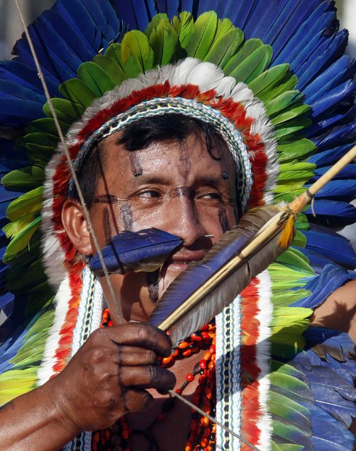 A member of indigenous group Kuikuro aims his arrow during the bow-and-arrow competition at the XII Games of the Indigenous People in Cuiaba November 10, 2013. 48 Brazilian Indigenous tribes will present their cultural rituals and compete in traditional sports such as archery, running with logs and canoeing during the XII Games of Indigenous People which will run until November 16. (Photo by Paulo Whitaker/Reuters)