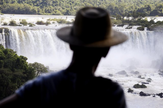 "In this March 14, 2015 photo, a tourist looks at Iguazu Falls in Brazil. Spaniards came across the Iguazu Falls in 1541. In Guarani, its name means ""big water"". The falls are on the border between Misiones province in Argentina and Parana in Brazil. (Photo by Jorge Saenz/AP Photo)"