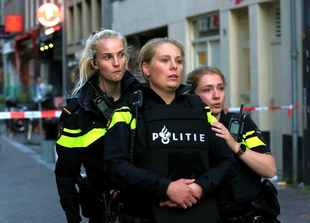 Police officers look on as they stand guard to secure the area where Dutch celebrity crime reporter Peter R. de Vries, known for his reporting on some of the most renowned criminals in the Netherlands, was reportedly shot and seriously injured, in Amsterdam, Netherlands, July 6, 2021. (Photo by Eva Plevier/Reuters)