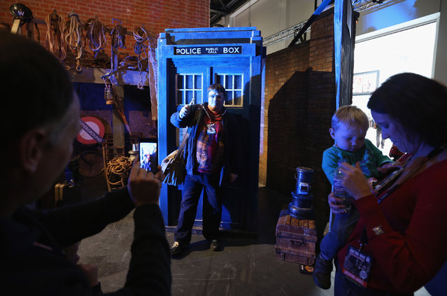 """Doctor Who fans pose for a photograph in front of a model of the TARDIS at the """"Doctor Who 50th Celebration"""" event in the ExCeL centre on November 22, 2013 in London, England. (Photo by Oli Scarff/Getty Images)"""