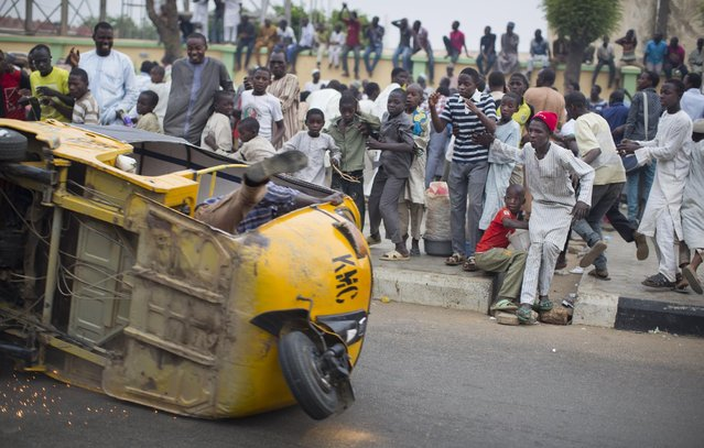 Supporters of opposition candidate Muhammadu Buhari look on as a three-wheeled passenger taxi, driving wildly in celebration of an anticipated Buhari win, screeches to a halt after flipping over on its side while driving in Kano, Nigeria Tuesday, March 31, 2015. (Photo by Ben Curtis/AP Photo)