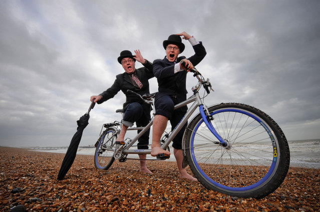 "City gents limber up on Brighton beach with their tandem before competing in ""The Rat Race"" event . (Photo by Jim Holden/Alamy Stock Photo)"