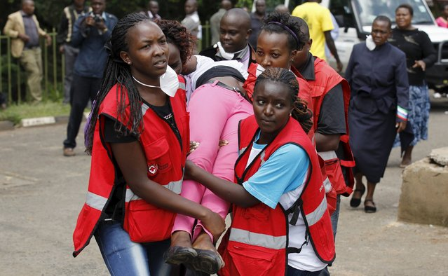 """A relative is assisted by Kenya Red Cross staff where bodies of students killed in Thursday's attack by gunmen, are preserved at the Chiromo Mortuary in the capital Nairobi April 4, 2015. Somali militants vowed on Saturday to wage a long war against Kenya and run its cities """"red with blood"""" after the group's fighters killed nearly 150 people during an assault on a Kenyan university. (Photo by Thomas Mukoya/Reuters)"""
