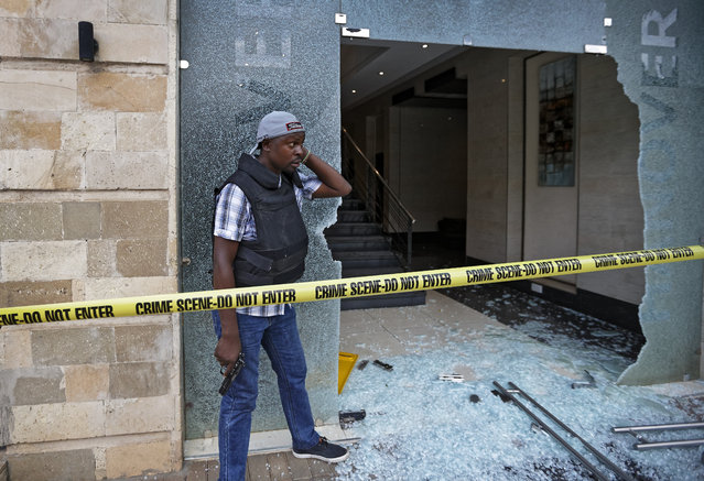 A plain-clothed member of security forces stands by the entrance to a hallway in which an unexploded grenade lies, at a hotel complex in Nairobi, Kenya Tuesday, January 15, 2019. Terrorists attacked an upscale hotel complex in Kenya's capital Tuesday, sending people fleeing in panic as explosions and heavy gunfire reverberated through the neighborhood. (Photo by Ben Curtis/AP Photo)