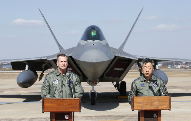 U.S. Forces Korea deputy commander and U.S. Seventh Air Force commander, Lt. Gen. Terrence O'Shaughnessy, left, listens to Lt. Gen. Lee Wang-kuen, Air Force commander, while speaking to the media near the one of four U.S. F-22 stealth fighter after landing at Osan Air Base in Pyeongtaek, South Korea, Wednesday, Feb. 17, 2016. Four U.S. F-22 stealth fighters flew over South Korea on Wednesday in a clear show of power against North Korea. (Photo by Lee Jin-man/AP Photo)