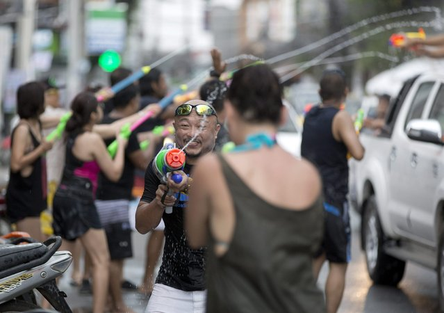 Tourists and locals exchange water pistol fire during the Songkran festival to celebrate the Thai New Year on Samui Island in Surat Thani province, Thailand, Monday, April 13, 2015. The Songkran festival, also known as the Thai New Year or Thailand Water Festival, was originally celebrated as a way for the Thai people to sprinkle water on their family members and elders for good fortune and pay their respects to images of the beloved Buddha. (Photo by Mark Baker/AP Photo)