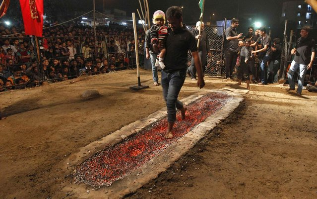 Shiite Muslim carry a child barefoot across hot coals during a ceremony known as Arbain in the city of Ahmedabad, India, on December 24, 2013. (Photo by Amit Dave/Reuters)