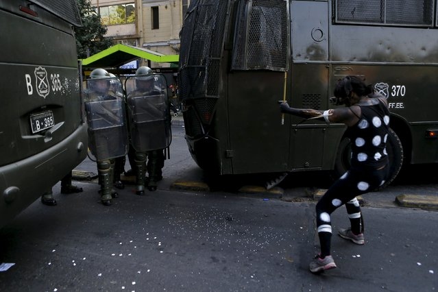 A protester dressed as a Patagonian native Indian points to riot police during a demonstration to demand changes in the education system at Santiago, April 16, 2015. (Photo by Ivan Alvarado/Reuters)