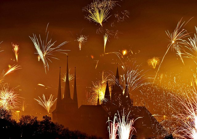 Fireworks light the sky above the Mariendom (Cathedral of Mary), right, and the St. Severi's Church in Erfurt, Germany. (Photo by Jens Meyer/Associated Press)