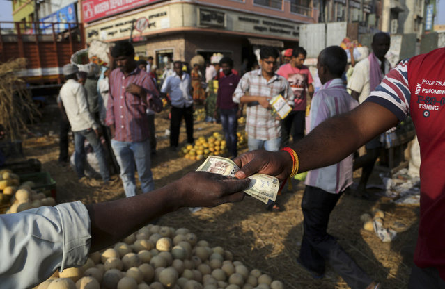 People trade at a wholesale fruit market in Bangalore, India, Monday, February 29, 2016. India has pledged to invest billions of dollars to improve the lives of farmers and boost the rural economy, boost consumer demand and stimulate growth. Finance Minister Arun Jaitely proposed spending nearly $13 billion on rural development, promising higher incomes for farmers who form the majority of India's 1.2 billion. (Photo by Aijaz Rahi/AP Photo)