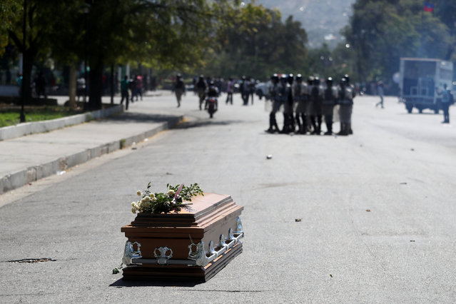 The casket of a man shot dead during anti-government protests lies on the ground as riot police release tear gas to disperse locals residents in Port-au-Prince, Haiti, February 22, 2019. (Photo by Ivan Alvarado/Reuters)