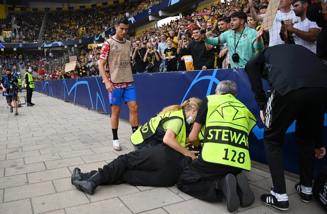 A security guard lies injured after a shot taken from Cristiano Ronaldo of Manchester United during the warm up makes contact with him during the UEFA Champions League group F match between BSC Young Boys and Manchester United at Stadion Wankdorf on September 14, 2021 in Bern, Switzerland. (Photo by Matthias Hangst/Getty Images)