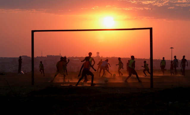Locals play soccer on a dusty pitch in Soweto, South Africa, September 15, 2021. (Photo by Siphiwe Sibeko/Reuters)