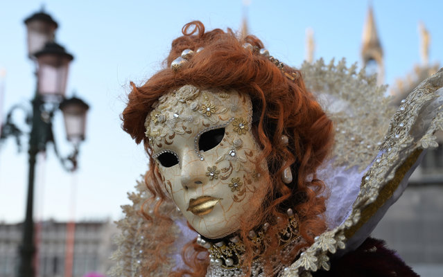 A masked reveller poses in Venice's Riva degli Schiavoni on the opening day of the Venice Carnival on February 17, 2019. The carnival in Venice takes place until March 5, 2019. (Photo by Vincenzo Pinto/AFP Photo)
