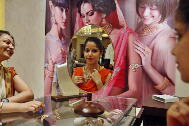 """An Indian customer, reflected on a mirror, tries a gold necklace at a jewelry shop in Allahabad, India, Tuesday, April 21, 2015. Tuesday marks the Hindu festival """"Akshay Tritiya"""" considered auspicious for buying gold among other things. (Photo by Rajesh Kumar Singh/AP Photo)"""