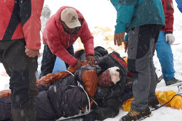 In this photograph taken on April 25, 2015, rescuers tend to a sherpa injured by an avalanche that flattened parts of Everest Base Camp. Rescuers in Nepal are searching frantically for survivors of a huge quake on April 25, that killed nearly 2,000, digging through rubble in the devastated capital Kathmandu and airlifting victims of an avalanche at Everest base camp. (Photo by Roberto Schmidt/AFP Photo)