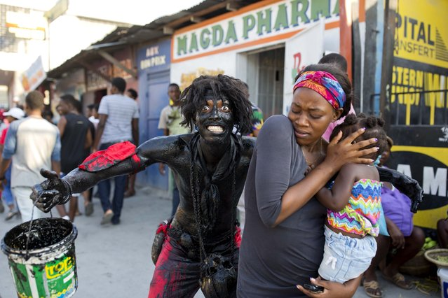 A reveler dressed as a devil with his body smothered with mud and oil, scares a woman and her daughter during the Carnival parade in the Carrefour district of Port-au-Prince, Haiti, Tuesday, March 5, 2019. (Photo by Dieu Nalio Chery/AP Photo)