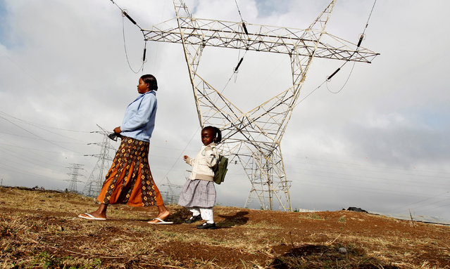 A woman walks her child to school past high voltage electrical pylons on the outskirts of Kenya's capital Nairobi, March 14, 2011. (Photo by Thomas Mukoya/Reuters)