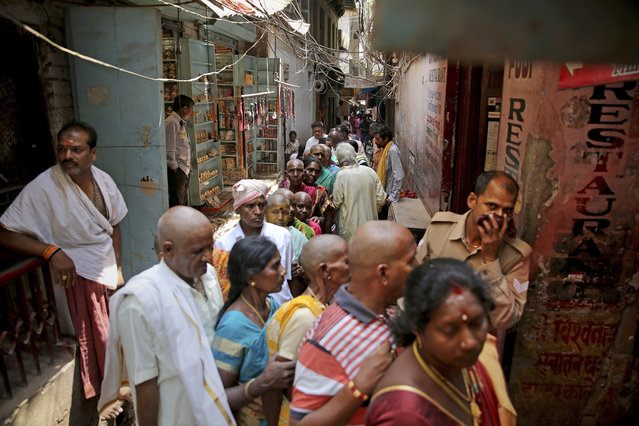 In this March 22, 2019, photo, Hindu devotees stand in queue in a narrow lane to enter into Vishwanath temple, in Varanasi, India. In the Indian city considered the center of the Hindu universe, Prime Minister Narendra Modi has commissioned a grand promenade connecting the sacred Ganges river with a centuries-old Vishwanath temple dedicated to Lord Shiva, the god of destruction. (Photo by Altaf Qadri/AP Photo)
