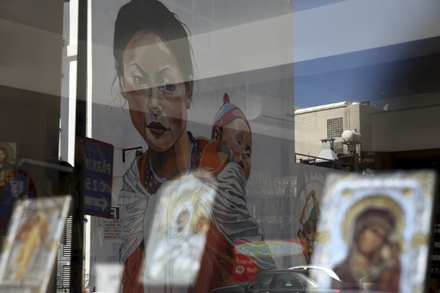 "A street mural depicting a Nepalese woman with a baby on her back by Greek street artist Achilleas Michaelides, alias ""Paparazzi"", is reflected in a shop window in which Greek Orthodox icons are displayed in the coastal town of Limassol, Cyprus May 7, 2015. Michaelides created the mural in tribute to earthquake-stricken Nepal. (Photo by Yiannis Kourtoglou/Reuters)"