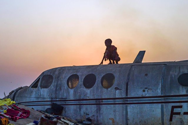"""A boy stands on an airplane in the Christian Mpoko refugee camp on February 20, 2014 during sunset, in Bangui, Central African Republic. Interim President Samba Panza has vowed to """"go to war"""" on the anti-balaka, who claim to seek vengeance for atrocities committed by a mainly Muslim rebel alliance, the Seleka, which temporarily seized power in March last year. (Photo by Fred Dufour/AFP Photo)"""