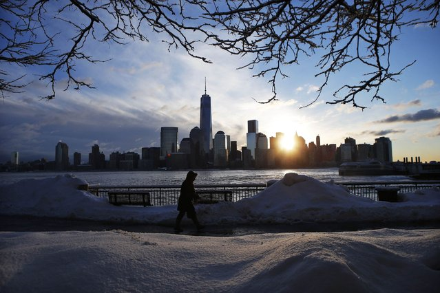 The New York skyline and the One World Trade Center are seen in the distance as a man makes his commute after a night of snow from New York City to Exchange Place in New Jersey. (Photo by Eduardo Munoz/Reuters)