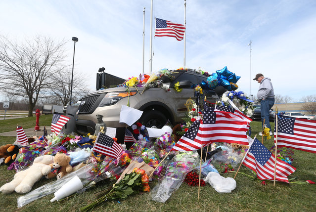Retired Howard County Sheriff Deputy Jon Zeck admires the outpouring community support of flowers, stuffed animals, American flags, and messages that decorate Deputy Carl Koontz's patrol car in front of the Howard County Sheriff's Department in Kokomo, Ind., Tuesday, March 22, 2016. Koontz was killed early Sunday, March 20, 2016, during a gunfight inside a mobile home in Russiaville while he was helping serve arrest and search warrants. (Photo by Kelly Lafferty Gerber/The Kokomo Tribune via AP Photo by )