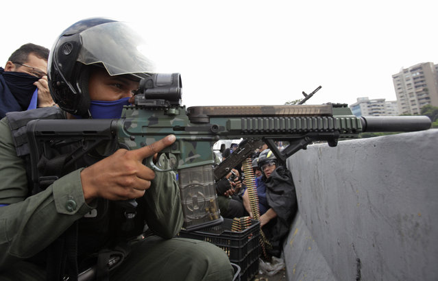 A rebel soldier who is part of a group rising up against the government of Venezuela's President Nicolas Maduro aims his weapon from an overpass at La Carlota military airbase where loyal troops are located, as members of the press and civilians take cover in Caracas, Venezuela, Tuesday, April 30, 2019. (Photo by Boris Vergara/AP Photo)
